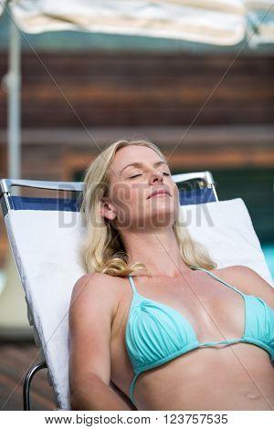 Beautiful woman in bikini relaxing on a sun lounger near pool