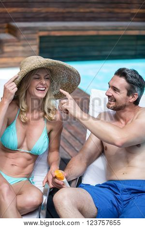 Man applying sunscreen lotion on woman's nose near the pool
