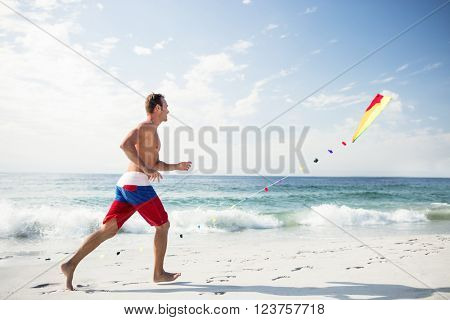Young man on beach playing with a kite on a sunny day