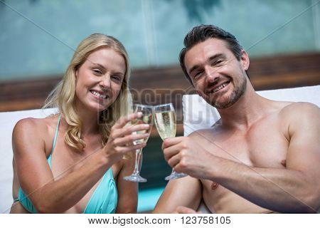 Couple sitting on sun lounger toasting champagne near the pool