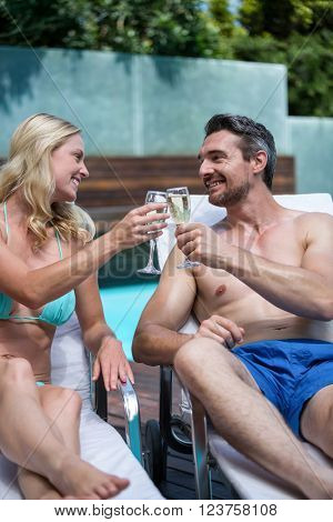 Couple sitting on sun lounger and toasting champagne glass near the pool
