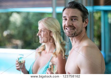 Happy couple having champagne near the pool
