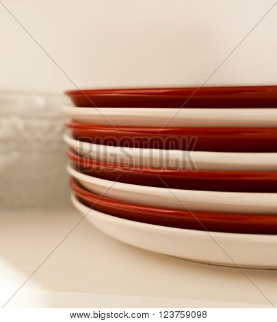 Stacked white and red plates and glass bowls