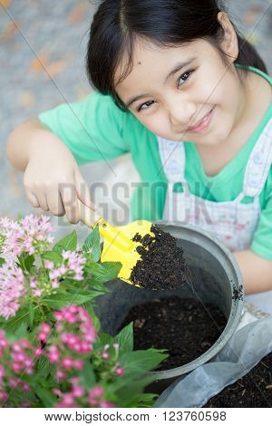 Little Asian child planting flower in the pot