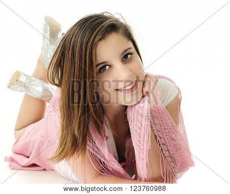 A beautiful young teen laying on her belly and looking up at the viewer with raised legs and sparkly heels behind.  On a white background.