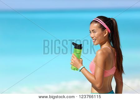 Healthy fitness runner girl drinking water from plastic bottle on running break. Young Asian woman happy on beach training cardio taking a rest during workout wearing a smart watch activity tracker.