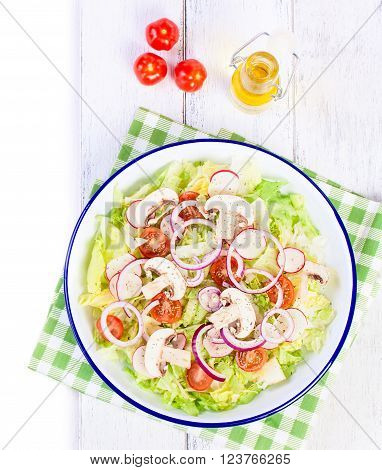 Healthy fresh summer salad with letucce radish cherry tomatoes red onion and champignons with italian herbs on a wooden background with olive oil top view with copy space