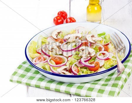 Healthy fresh summer salad with letucce radish cherry tomatoes red onion and champignons with italian herbs on a wooden background with olive oil closeup copy space