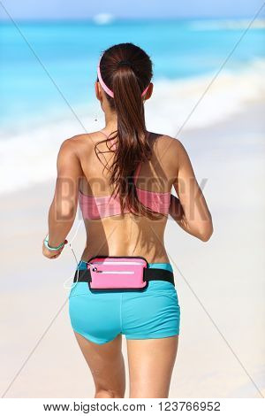 Active runner from being jogging with wearable tech running gear fanny pack smartphone holder belt for music listening with earphones jogging away in blue sport shorts and sports bra with ponytail.