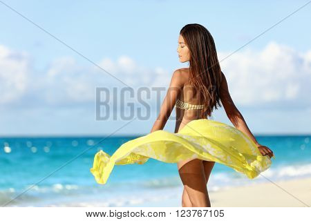 Carefree beautiful sexy bikini body woman relaxing in yellow flowing cover-up beachwear fashion wrap on ocean sunset background. Weight loss thighs cellulite and skincare spa beauty care concept.