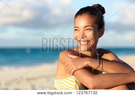 Happy healthy young Asian chinese woman smiling on beach enjoying relax lifestyle sitting in swimwear. Beautiful mixed race tourist in hair bun and golden jewelry at sunset on Caribbean travel. poster