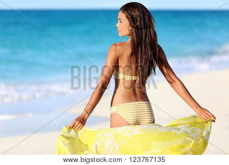 Beach woman relaxing in yellow bikini and cover-up pareo beachwear enjoying sunset. Beautiful Asian girl model from the back for suntan skincare or weight loss cellulite sexy body concept.