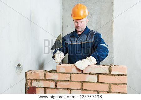 bricklayer at work with red brick
