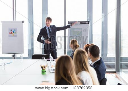 Business man showing ground-plan during meeting in modern office.