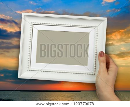 Wooden frame in beautiful woman hands on the background beautiful sunset