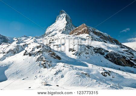 Scenic view on snowy Matterhorn peak in sunny day, Switzerland.