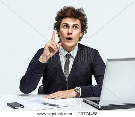 Exactly! Cool idea finally remembered. Businessman at the workplace working with computer on gray background.
