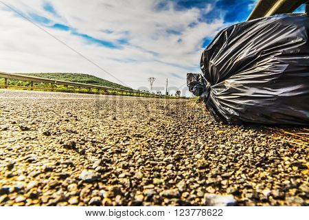 trash bag on the ege of a country road