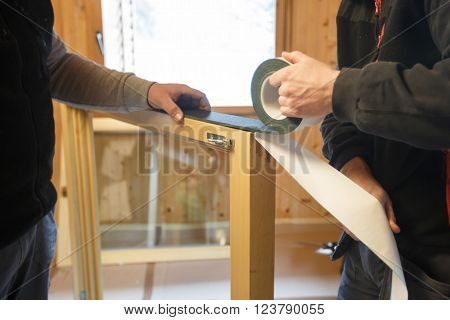 Workers applying a RAL self-adhesive insulating tape to install new three pane wooden windows in a wooden house. Home renovation sustainable living energy efficiency concept.