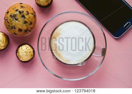Cup of cappuchino with cake and candies and smart phone on pink surface