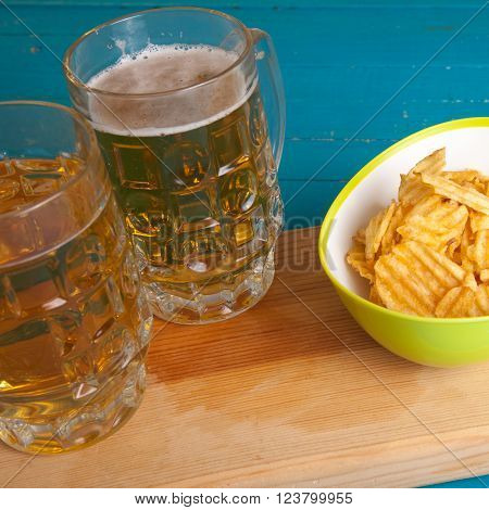 Potato Chips And Two Mugs Of Beer On The Table