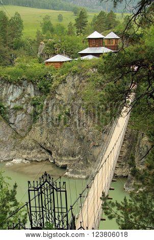 ALTAI RUSSIA - JUNE 11 2012: Suspension bridge to the monastery on the island of Patmos Altai Russia