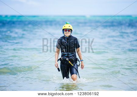 Female kiteboarder student walking in shallow water in sea