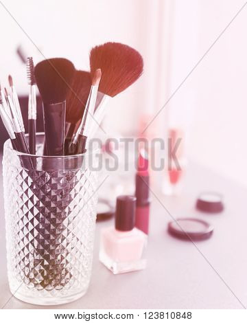 Makeup tools with cosmetics on a table, close up