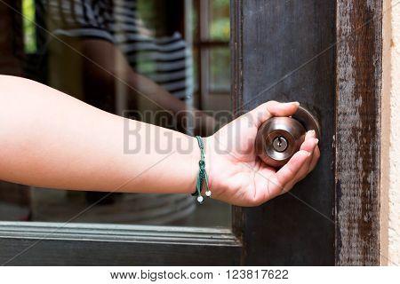 woman hand holding doorknob represent opening or closing door