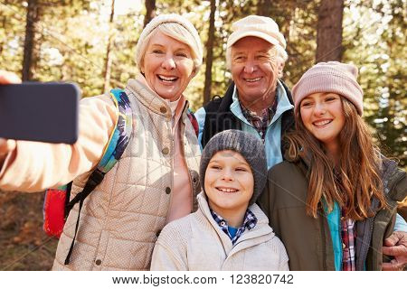 Senior woman taking outdoor selfie with grandkids and spouse