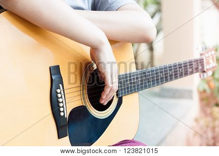 Woman's hands with acoustic guitar in relax post, stock photo