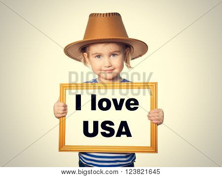Little Funny girl in striped shirt with blackboard. Text I love USA.  Isolated on gray background.