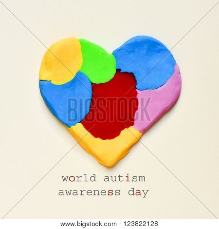 the text world autism awareness day and a heart made from modelling clay of different colors on an off-white background