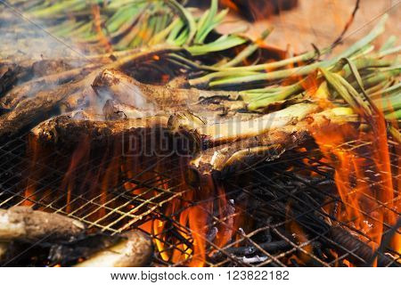 closeup of a pile of calcots, sweet onions typical of Catalonia, Spain being cooked in the barbecue