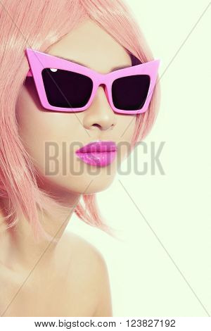 Vintage style portrait of young sexy asian girl with pink choppy bob haircut and fancy sunglasses, copy space