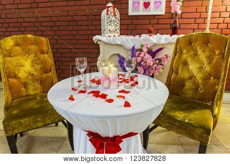 Romantic zone with round table with red petals and burning candles