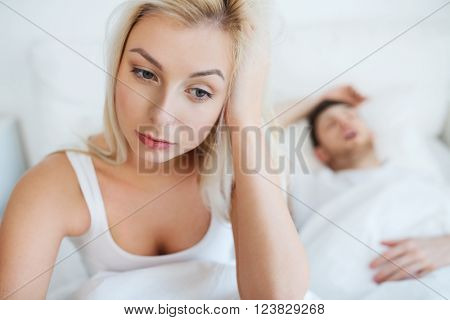 people, health, sleep disorder concept - couple in bed at home, man snoring and young woman suffering from insomnia