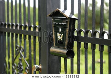 old mailbox fixed to the metal fence