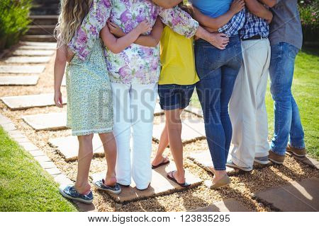 Rear view of multi-generation family standing with hands behind back in yard