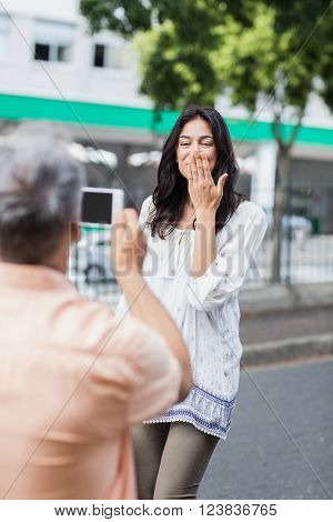 Rear view of man photographing happy woman blowing kiss in city