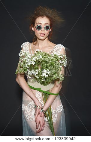 vogue fashion model woman with professional make up and hairstyle in sunglasses with flowers bouqet on dark background