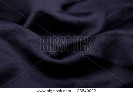 Black silk as a wavy black background (shallow DOF, selective focus on the curves)