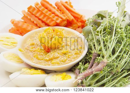 Solanum ferox, Solanum stramonifolium or Hairy-fruited eggplant chili dip with siamese neem tree, carrot and egg on a white plate. ** Note: Shallow depth of field