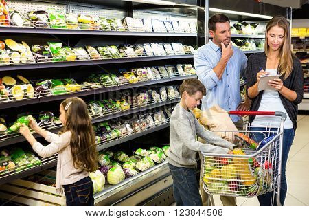 Cute family choosing groceries together in the supermarket