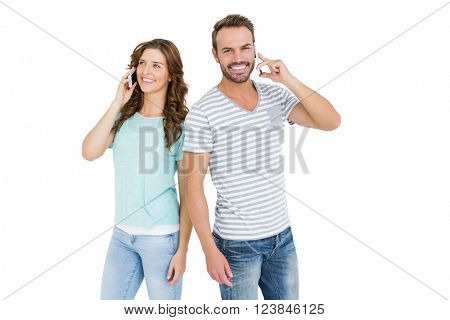Happy young couple talking on mobile phone on white background