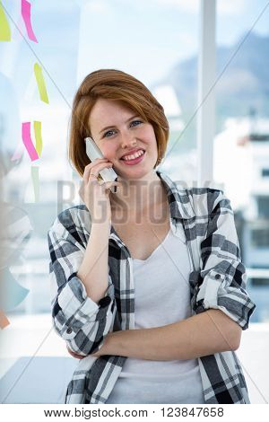 smiling hipster woman standing in her office making a phonecall