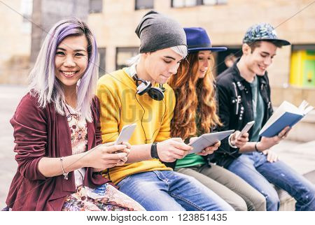 Multiethnic group of friends looking down at phone and tablet concepts about technology addiction and youth