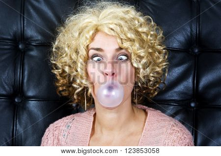 portrait of curly blond cross-eyed woman with bubblegum