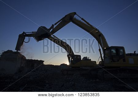 The bucket excavator and the excavator with a hammer are working on clearing the construction site