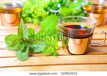 Peppermint tea medicinal herbs on the garden table